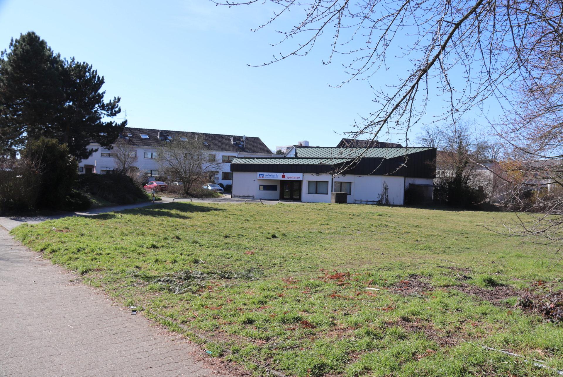 Teil des für ein Einkaufszentrum in Wixhausen vorgesehenes Areal, von der Schönbergstraße hergesehen. Im Hintergrund das von der Sparkasse mitgenutzte Volksbankgebäude.